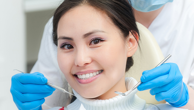 Woman receiving preventive dentistry to avoid dental emergencies