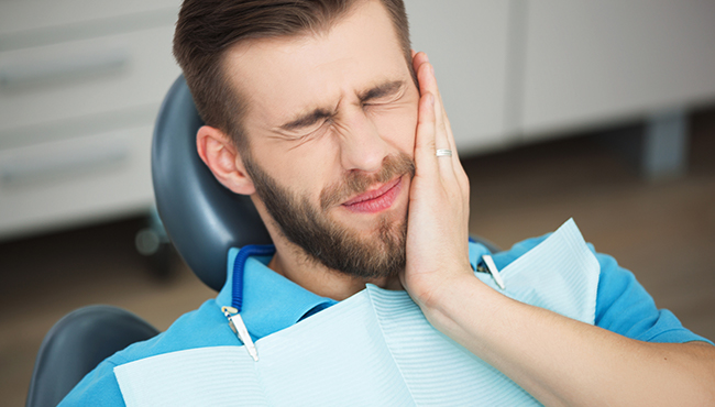 Man at emergency dentistry appointment holding jaw