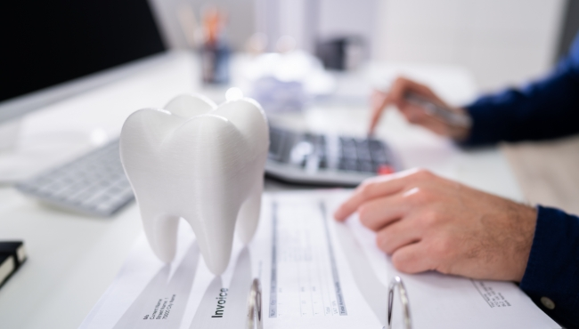 Dentist calculating the cost of dental implant tooth replacement