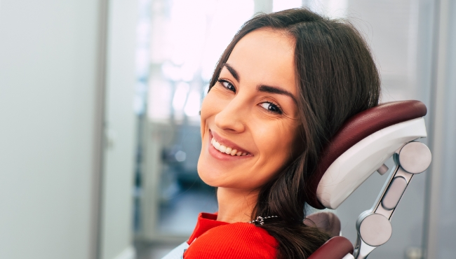 Woman smiling after dental implant tooth replacement