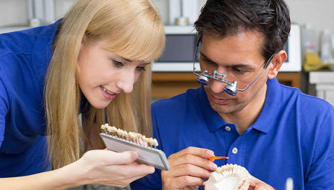 Dentist and dental implant specialist consulting on dental restoration