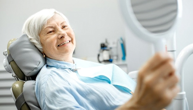 older woman using hand mirror to admire her dental implants in Ft. Worth