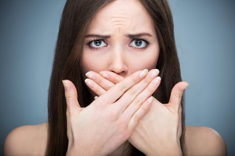 Woman covering cosmetic dental flaws
