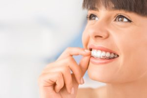 woman smiling inserting Invisalign in Fort Worth